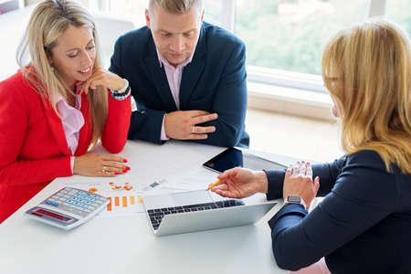 Mąż i żona omawiają plany inwestycyjne z doradcą finansowym