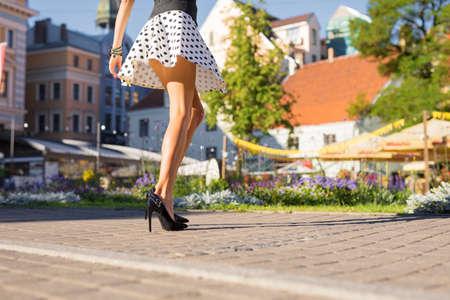Mujer con hermosas piernas con falda y tacones