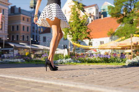Woman with beautiful legs wearing skirt and heels