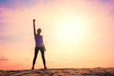 Happy woman celebrating success, silhouette against colorful sky with sunlight.