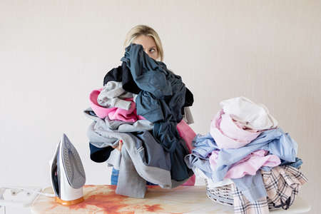 Woman at ironing desk behind pile of clothes