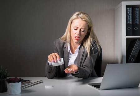 Woman taking drugs at work Stock Photo