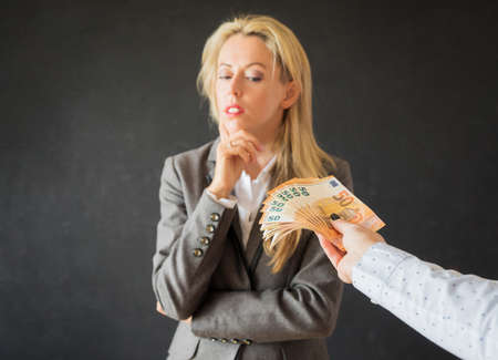 Woman thinking about accepting bribe money