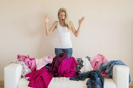 Desperate woman looking at mess on her couch Stock fotó - 115961443