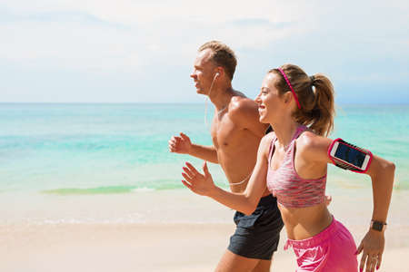Man and woman running on beach together Stock Photo