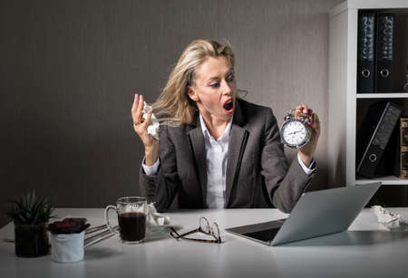 Woman at office in stress about deadline Фото со стока