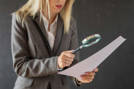 Woman carefully reading business contract with magnifying glass Imagens