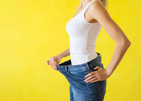 Woman showing her big trousers after successful diet and weight loss