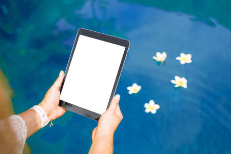 Woman sitting by the pool and using tablet computer. Vertical white screen . Фото со стока