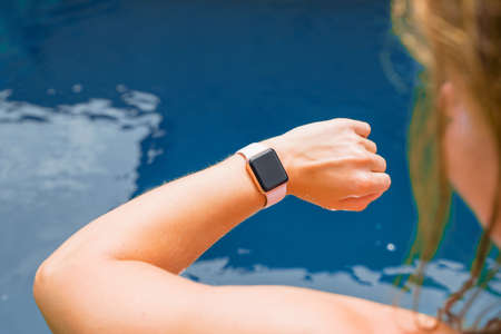 Woman wearing digital watch on hand by the pool 스톡 콘텐츠