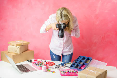 Woman taking photos of her own created products for putting them on sale online