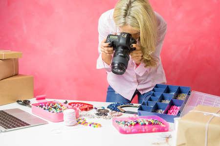 Mujer que toma fotos de su propia mercancía creada, las vende en línea y envía paquetes por correo a los compradores. Foto de archivo