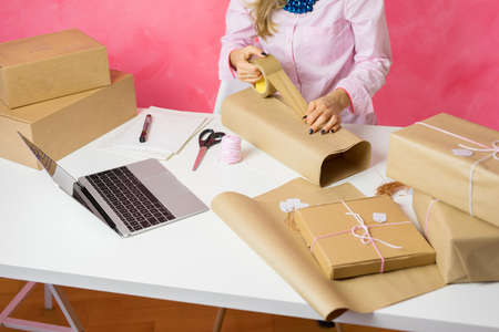 Woman selling items online and packaging goods for shipping.