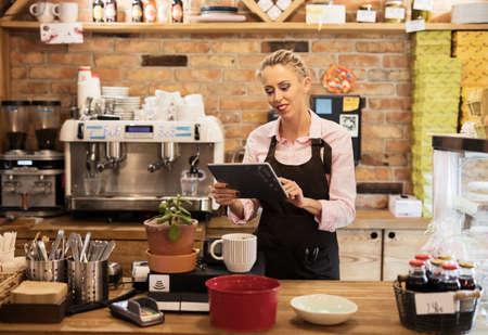 Woman using tablet computer in cafe Banco de Imagens