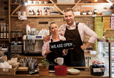 Couple in their new cafe, proud news business owners Banco de Imagens