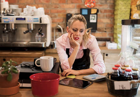 Worried new business owner calculating finances