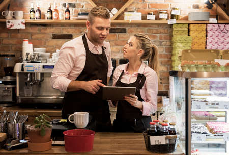 New business owners in cafe using tablet
