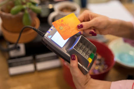 Waitress taking payment from credit card wirelessly on POS terminal Banco de Imagens
