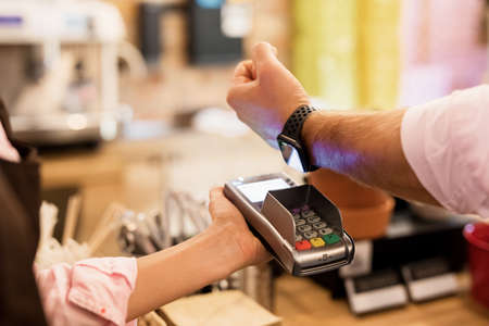 Person paying at cafe with smart watch wirelessly on POS terminal Foto de archivo