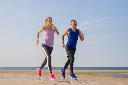 Runners fitness couple running training on the beach