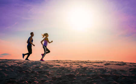 Silhouette of people jogging at sunset