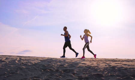 Two people jogging at sunset Banco de Imagens