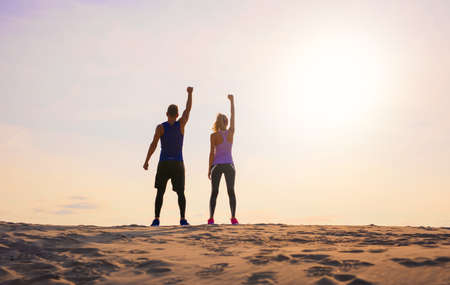 Fitness man and woman with arms up celebrating sport goals