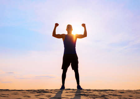Fitness male athlete with arms up celebrating success and goals