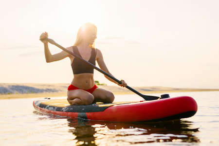 Happy woman on paddle board at sunset Banco de Imagens