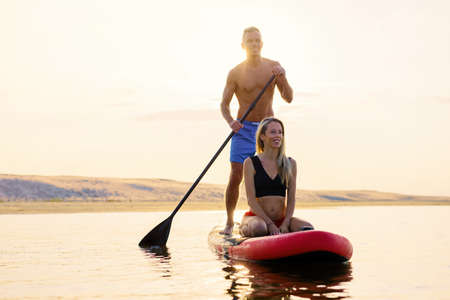 Couple relaxing together on paddle board Banco de Imagens