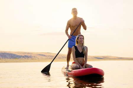 Paar entspannt sich gemeinsam auf dem Paddle Board