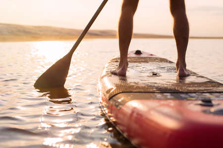 Person on paddle board at sunset Banco de Imagens