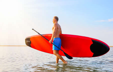 Man walking in the water with SUP board Banco de Imagens