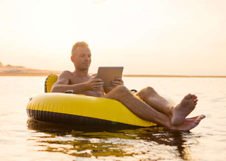 Man with a tablet on inflatable ring in the water at sunset Banco de Imagens