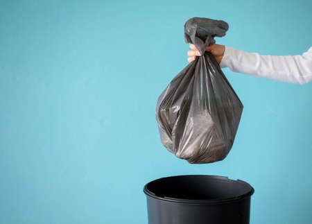 Hand holding garbage in plastic bag Banco de Imagens