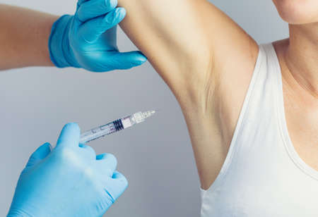 The doctor making intramuscular injection with syringe of botulinum toxin in the armpit against hyperhidrosis.