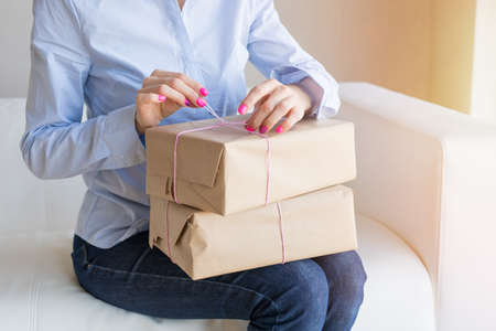 Woman unpacking delivery boxes with merchandise from online orders