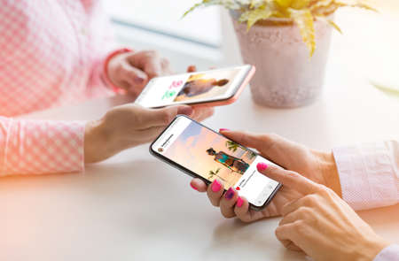 Two women using their mobile phones together Banco de Imagens