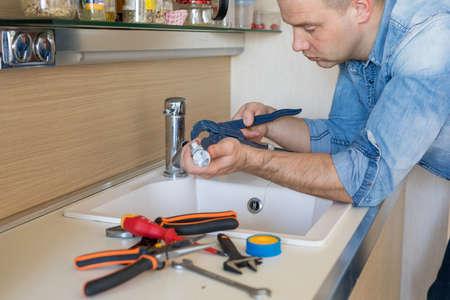 Man fixing leaking tap in kitchen