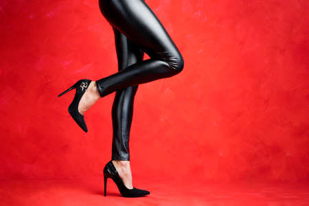 Woman with sexy legs wearing black leather pants and black high heel shoes on red background