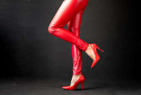 Woman with sexy legs wearing red leather pants and red high heel shoes on black background