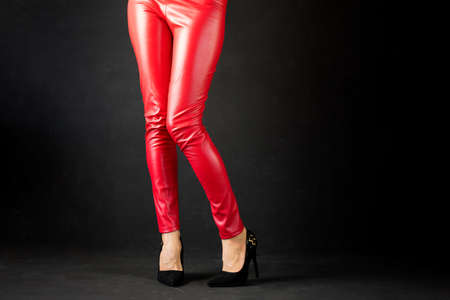 Woman in red leather pants and red high heel shoes
