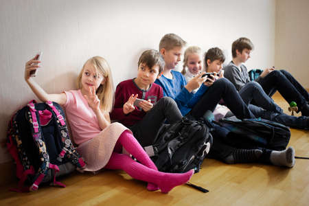 Portrait of cheerful girls and boys playing with phones
