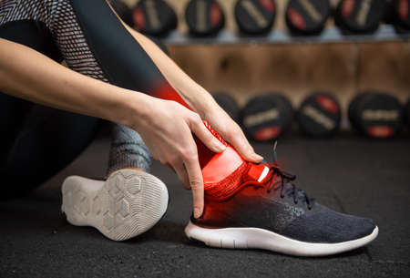 Woman with ankle injury in gym
