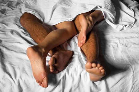 Legs of loving couple cuddling in bed under the sheets 写真素材
