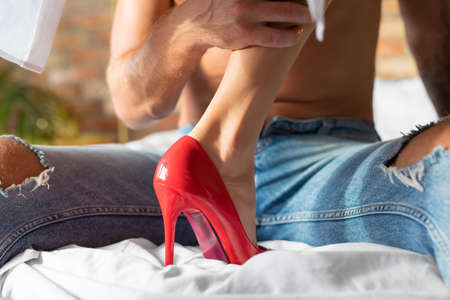 Passionate woman seducing her man by wearing red heels in bedroom