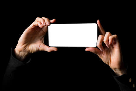 Person holding in both hands mobile phone horizontally with blank white screen, photo isolated on black background