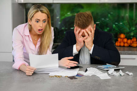 Couple reading terrible news regarding their finances