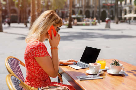 Business woman working with laptop and talking on the phone in cafe