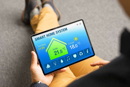 Man controlling home's appliances remotely by using smart home app on tablet computer
